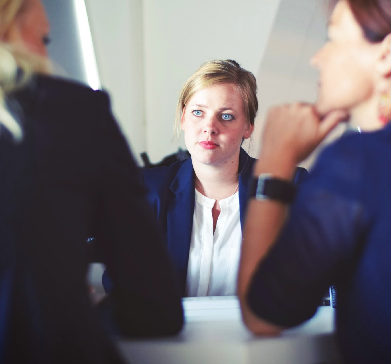 A woman looking across a table in the workplace at two women